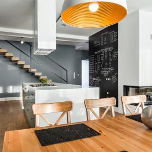 Delikatna kuchnia w stylo soft loft. Industrialna stylistyka przeplata się tutaj z przytulniejszym, domowym wystrojem. Jasnoszare meble kuchenne zestawiono z szarą ścianą w otwartej klatce schodowej. Otwarcie schodów na kuchnię również dodaje przestrzeni bardziej przemysłowy charakter. Fot. Pracownia Mebli Vigo.