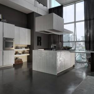Ciemnoszara betonowa podłoga, o ton ciemniejsze ściany i na ich tle wyeksponowane minimalistyczne, jasne meble. Całość utrzymano w chłodnych odcieniach, a przestronność wnętrza, wysokie okna oraz dominacja szarości nadają kuchni industrialny wyraz. Fot. Marchetti, kuchnia Torcolato.