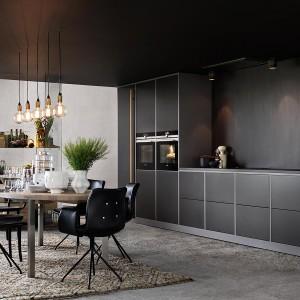 Prosty kształt i ciemna, chłodna barwa mebli kuchennych idealnie pasuje do industrialnej stylistyki i harmonizuje z surową powierzchnią nad blatem. Oświetlenie w postaci odsłoniętych żarówek również wprowadza do wnętrza stylistykę industrialną. Projekt: Mija Kinning. Fot. Ballingslov.