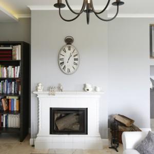 Ścianę nad kominkiem zdobi oryginalny, dekoracyjny zegar. We wnękę koło kominka wpasowano z kolei niewielką biblioteczkę.  Projekt: Beata Ignasiak. Fot. Bartosz Jarosz