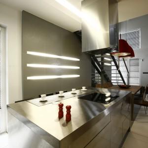Stal ponad wszystko - chce się powiedzieć, wkraczając do tej ultra nowoczesnej, industrialnej kuchni. Zarówno blat jak i fronty wyspy kuchennej wykonano ze stali nierdzewnej, która znalazła się również na ścianie w postaci stalowego panelu. Nad stołem jadalnianym natomiast, zawisły czerwone, loftowe lampy. Projekt: Liliana Masewicz-Kowalska. Fot. Bartosz Jarosz.