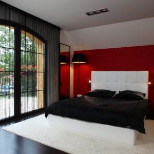 Nastrojowe, czarno-białe wnętrze z elementem zmysłowej czerwieni. Ochronę przed wzrokiem sąsiadów oraz nadmiarem światła zapewniają tzw. firanki makarony w eleganckim, czarnym kolorze. Projekt: Anna Kuk-Dutka. Fot. Bartosz Jarosz.