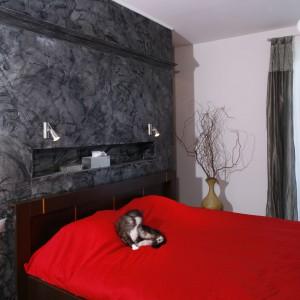 Szarą ścianę imitującą kamień efektownie równoważy narzuta na łóżko w kolorze ognistej czerwieni. Projekt: Katarzyna Merta-Korzniakow. Fot. Monika Filipiuk-Obałek.