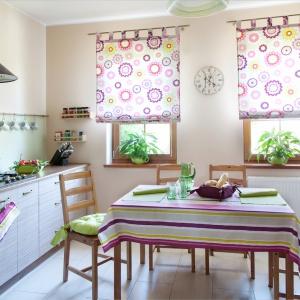 Fiolet i zieleń to ciekawe połączenie. Kolorowe kwiaty na roletach, paski na obrusie, zielone poduszki na krzesła - to wszystko oferuje sklep Dekoria. Użycie tkanin to prosty sposób na odświeżenie wnętrza. Fot. Dekoria.