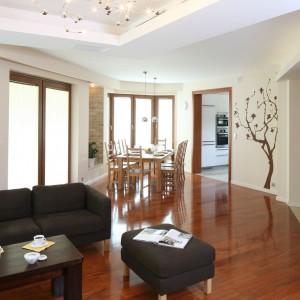 Przedłużeniem salonu jest elegancka jadalnia. Jedność tych dwóch pomieszczeń podkreśla podłoga wykończona drewnem. Fot. Bartosz Jarosz.