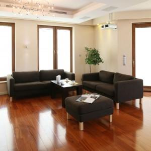 Nowoczesne meble w kolorze czekolady, oparte na geometrycznych, drewnianych nóżkach, wpisują się w prostą stylistykę pokoju dziennego. Fot. Bartosz Jarosz.