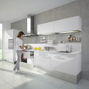 Białe, delikatne, nowoczesne meble pięknie harmonizują ze ścianą w strukturze betonu, w którą zostały wpasowane. Dolna zabudowa jest minimalnie wysunięta w stosunku do górnych szafek. Z jednej strony zabudowę zamykają dwa słupki ze sprzętem AGD. Fot. Nolte.