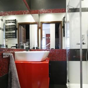 Ogromne lustra na ścianie powiększają przestrzeń małej łazienki. Czerwone akcenty natomiast doskonale ją ożywają. Projekt: Marta Kilan. Fot. Bartosz Jarosz.