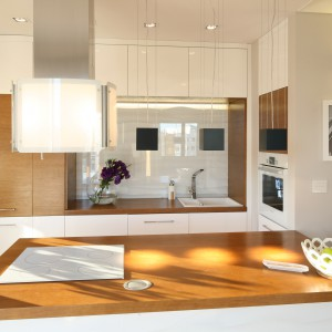 Drewniany blat jest eleganckim akcentem w kuchni. Jednocześnie ociepla wizualnie białą aranżację. Projekt: Karolina Łuczyńska. Fot. Bartosz Jarosz.