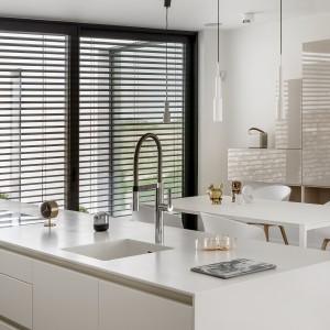 Piękna biała kuchnia zyskała również biały blat. Wykonany z Corianu, pięknie wpisuje się w nowoczesny styl mebli. Zastosowany materiał pozwolił na wyżłobienie komory zlewozmywaka w blacie. Fot. Zajc Kuchnie, kuchnia Z7/026.