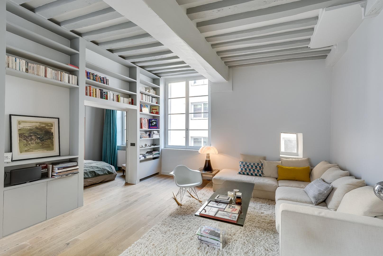 We wnętrzu dominują jasne kolory. Dębowa podłoga ma barwę, jasnego beżu, ściany są białe, meble wypoczynkowe kremowe. Nie jest jednak sterylnie, a bardzo przytulnie - za sprawą miękkim tekstyliów i drewnianych akcentów. Projekt: Tatiana Nicol. Fot. Meero Photographe Immobilier.