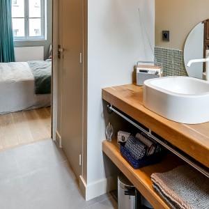 Łazienkę urządzono w duchu klasycznej prostoty. Nablatowa umywalka w kolorze tradycyjnej bieli i niewielkie, okrągłe lustro za umywalką idealnie wpisują się w charakter wnętrza dla mężczyzny. Projekt: Tatiana Nicol. Fot. Meero Photographe Immobilier.