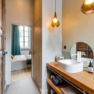 W aranżacji pomieszczeń panuje konsekwencja stylistyczna. Oświetlenie w łazience nawiązuje stylistyką i kolorem do lamp wiszących w jadalni. Projekt: Tatiana Nicol. Fot. Meero Photographe Immobilier.