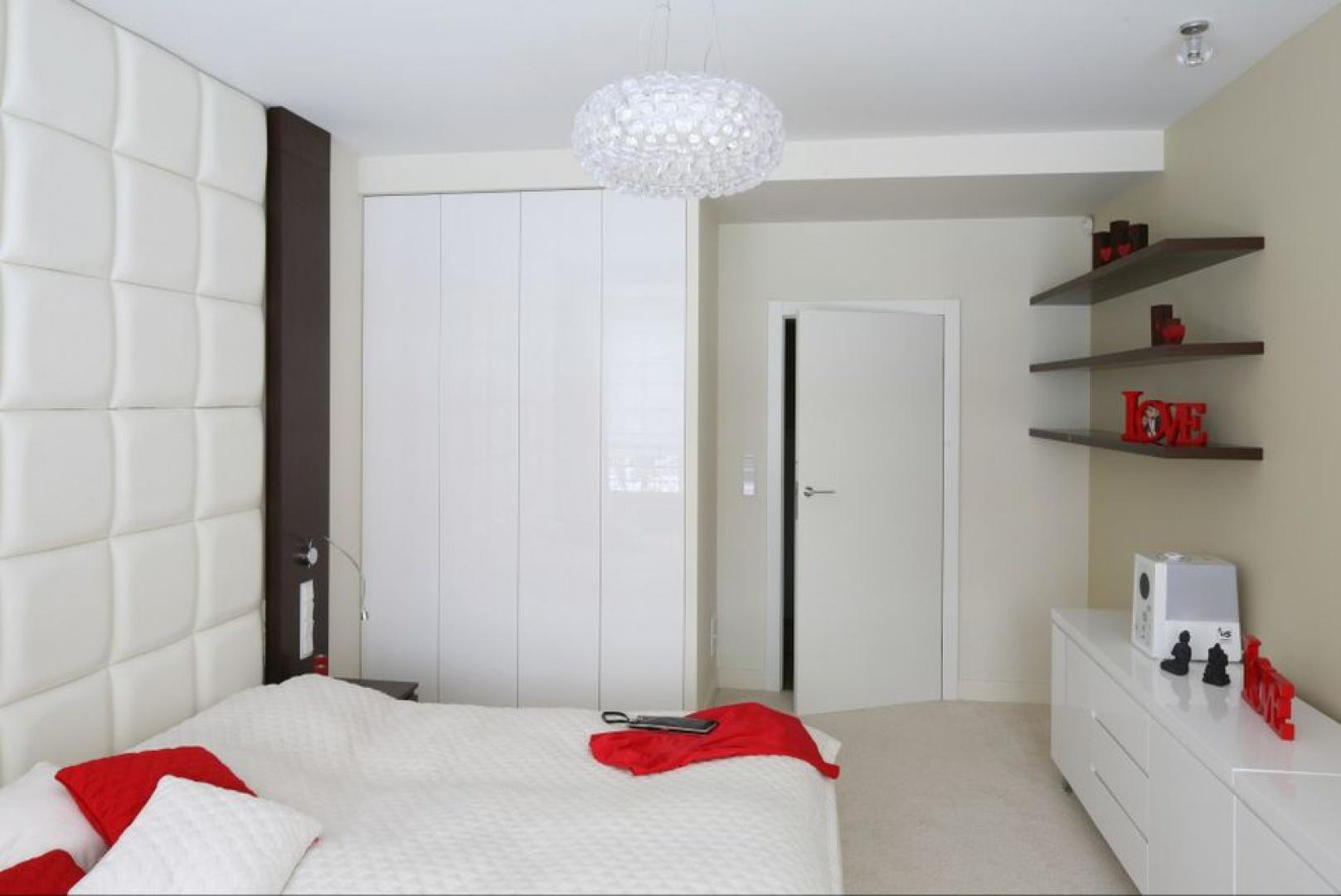 Biała, wysoka zabudowa z połyskującym frontami powiększa optycznie wnętrze sypialni. Jest idealnie dopasowane do pozostałych mebli w sypialni. Projekt: Katarzyna Mikulska-Sękalska. Fot. Bartosz Jarosz