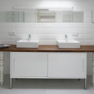 W tej łazience chłód i sterylność bieli przełamuje drewno, które doskonale ociepla wnętrze. Prostej w formie szafce finezji dodają ozdobne nóżki. Projekt: Konrad Grodziński. Fot. Bartosz Jarosz.