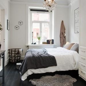 Drewniana podłoga pomalowana czarną farbą to rozwiązanie dla wszystkich stawiających na oryginalność. Tworzy ona przyjemny kontrast z jasnymi ścianami. Fot. Alvhem Mäkler.