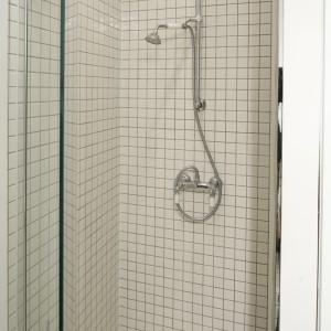 Cała strefa prysznica wyłożona została białą mozaiką. Stylizowana bateria pasuje do niej idealnie. Projekt: Agnieszka Żyła. Fot. Bartosz Jarosz.