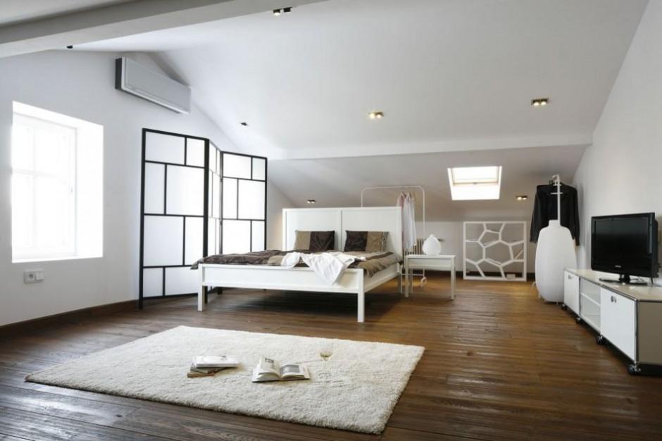Przestronną, jasną sypialnię urządzoną w nowoczesnym stylu ociepla drewniana podłoga. Jej ciemne wybarwienie doskonale pasuje co białych ścian. Projekt: Konrad Grodziński. Fot.Bartosz Jarosz.