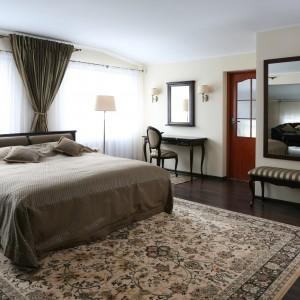 Ciemną, drewnianą podłogę zdobi jeszcze dodatkowo duży dywan z dekoracyjnym wzorem. Takie zestawienie świetnie pasuje do eleganckiej sypialni w klasycznym stylu. Projekt: Małgorzata Goś. Fot. Bartosz Jarosz.