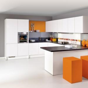 Biel tej kuchni ożywiono akcentami kolorystycznymi w barwie żywego pomarańczu. W zestawie z bielą i ciemnym blatem tworzą razem elegancką i energetyzującą kompozycję. Ponieważ meble kuchenne utrzymano w minimalistycznym wzornictwie, całość nie razi przesadą. Fot. Brigitte.