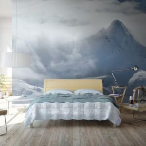 Fototapeta z widokiem na górski krajobraz. Delikatne połączenie szarości, błękitów i bieli wprowadza do sypialni łagodny nastrój. Fot. Myloview.
