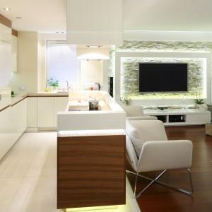 W zintegrowanej strefie dziennej kuchnia płynnie łączy się z salonem. Wszechobecna biel powiększa optycznie jej przestrzeń, a dekor drewna ją wizualnie ociepla. Projekt: Małgorzata Mazur. Fot. Bartosz Jarosz.