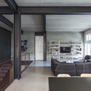 Na parterze, będącym drugą kondygnacją apartamentu, urządzono otwartą strefę dzienną. Na przestronnym open space urządzono stylowy salon i nowoczesną kuchnię. Projekt: Pitsou Kedem Architects. Fot. Amit Geron.