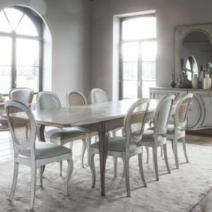 Piękny, stylizowany stół z ozdobnymi nogami i dekoracyjnym wykończeniem blatu. Utrzymany w jasnej tonacji, która nadaje mu lekkiego wyrazu. Z kolei eleganckie zdobienia sprawiają, że jest idealny do barokowych wnętrz. Fot. Grange, kolekcja mebli Medaillon.