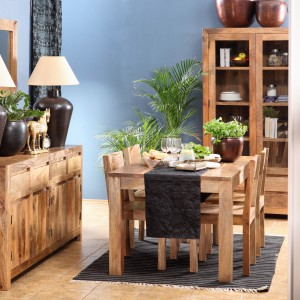Drewniany stół w jasnym, przytulnym kolorze miodowego brązu z widocznym rysunkiem słojów drewna stwarza we wnętrzu bardzo przytulną, domową atmosferę. Fot. Sharda Home/Domoteka.
