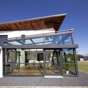 Wielkowymiarowe przeszklenia to doskonały sposób na uwspółcześnienie bryły domu. Dobudowując do domu ogród zimowy, możemy dowolnie operować dużymi połaciami szkła, nadając im fantazyjne kształty. Fot. Schueco.