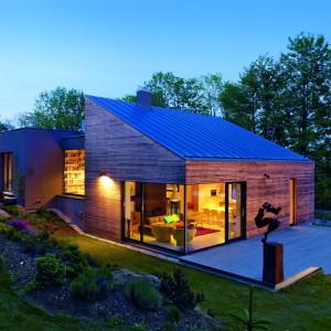 Piękny, nowoczesny dom. Prostą bryłę wieńczy blaszany dach, drewniana elewacja i duże, panoramiczne przeszklenia. Fot. Schueco.
