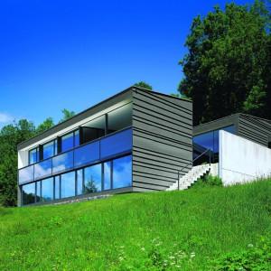 Blacha jako pokrycie dachowe jest popularna od wielu lat. Coraz częściej jednak sięgamy po nią również wówczas, gdy poszukujemy materiału elewacyjnego. Panele blaszane w połączeniu z przeszkloną niemal całkowicie ścianą, nadają domowi futurystyczny wygląd. Fot. Rheinzink.