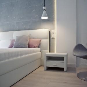 Tekstylny zagłówek nadaje przestrzeni sypialni przytulny charakter. Efektowne oświetlenie na ścianie, układające się w ramę, zamykającą betonowe płyty nad wezgłowiem, nadaje pomieszczeniu futurystyczny wyraz. Fot. RED Real Estate Development.