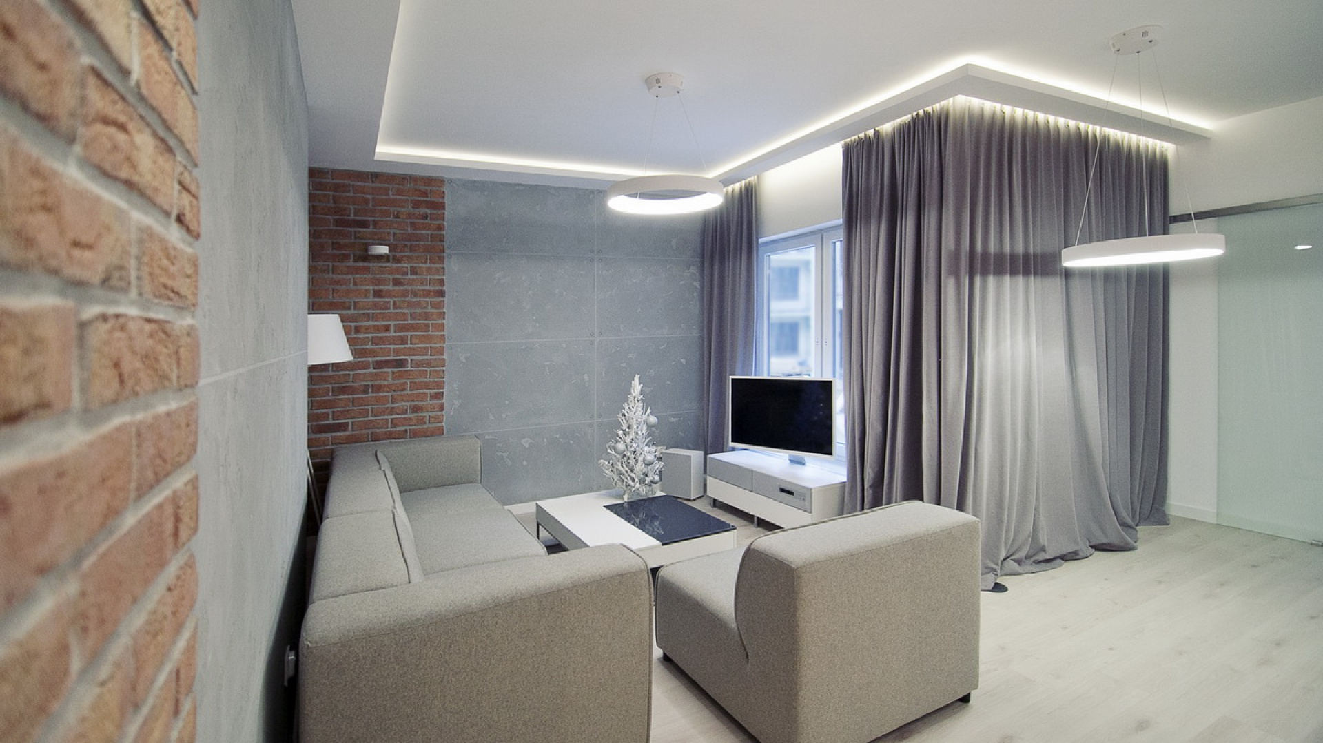 Ściany w salonie wykończono ręcznie wyrabianą cegłą i betonowymi płytami. Gra dwóch surowych, industrialnych materiałów nadaje pokojowi dziennemu loftowy klimat. Fot. RED Real Estate Development.