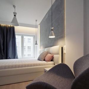 Zamiast tradycyjnych lampek nocnych, w sypialni zawisło dekoracyjne oświetlenie, luźno nawiązujące stylem do loftowych, technicznych lamp. Fot. RED Real Estate Development.