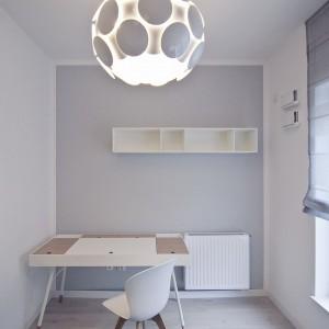 W gabinecie wzrok przyciąga efektowna lampa z oryginalnym abażurem o geometrycznym motywie. Fot. RED Real Estate Development.