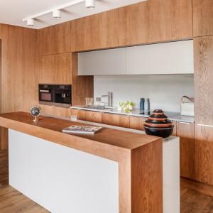 Piękna kuchnia, zainspirowana amerykańskim minimalizmem lat 50-tych. Dominujący w kuchni fornir przełamano jasnym kolorem konglomeratu Silestone. Wyspa jest nieduża, ale wyposażona w sporo podręcznych, praktycznych szuflad z organizerami. Nałożony na nią, dodatkowy blat jest praktyczny i efektownie się prezentuje. Fot. Zajc Kuchnie, model Z5.