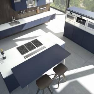 Kuchnia o oryginalnych barwach. Uniwersalną biel połączono z kolorem indygo. Kombinacja tych kolorów nadaje meblom elegancki charakter. A same meble są bardzo modne i praktyczne - z wyspą kuchenną, funkcjonującą jako powierzchnia gotowania oraz domowy bar. Fot. Pronorm, linia X-ML.