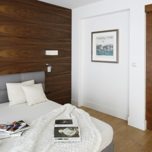 W sypialni jedną ścianę wykończono fornirem, pozostałe pomalowano na biały, kontrastujący kolor. Wnętrze dodatkowo ociepla dębowa podłoga. Projekt: Kamila Paszkiewicz. Fot. Bartosz Jarosz.