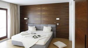 Nowoczesna sypialnia została urządzona w minimalistyczny, ale jednocześnie bardzo przytulny sposób. A wszystko dzięki dębowej podłodze, tapicerowanemu łóżku oraz ściana wykończonej fornirem azouke.
