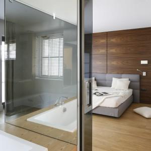 Sypialnię połączono z łazienką. Przestrzeń wydziela szklana ściana. Projekt: Kamila Paszkiewicz. Fot. Bartosz Jarosz.
