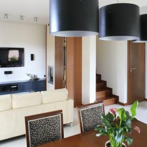 Jasna, nowoczesna sofa wyznacza granice salonu. Przestrzeń jadalni natomiast - trzy ciemne lampy sufitowe zawieszone nad stołem. Projekt: Aleksandra Wołczyk. Fot. Bartosz Jarosz.