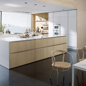 Piękna, nowoczesna kuchnia, w której dominują beże i szarości - najmodniejsze barwy w aranżacji wnętrz. Wyspa jest duża, ale o prostej, minimalistycznej formie, dzięki czemu nie przytłacza przestrzeni. Fot. SieMatic.