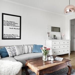 Biało-szary salon ociepla piękny, stylizowany stoli kawowy w pięknym kolorze drewna. Harmonizuje z nim dekoracyjna lampa w kolorze miedzi. Fot. Stadshem.se/Janne Olander.