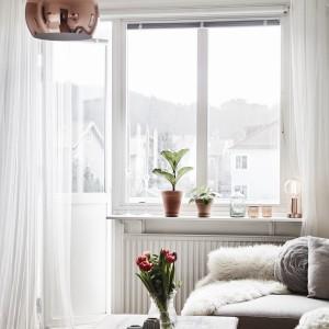 W salonie wzrok przykuwa dekoracyjna, elegancka lampa w kolorze miedzi. Fot. Stadshem.se/Janne Olander.