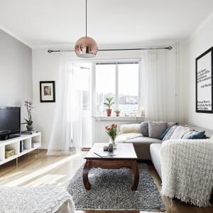 Dzięki jasnym kolorom i światłu wpadającemu do wnętrza przez duże przeszklenia balkonowe, salon wydaje się znacznie większy niż jest w rzeczywistości. Fot. Stadshem.se/Janne Olander.