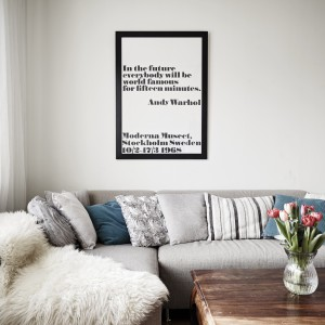 Przytulny nastrój w salonie budują tekstylia: dekoracyjne poduchy oraz narzuta-futerko. Poduszki dodatkowo wprowadzają akcent kolorystyczny do wnętrza, w którym dominują stonowane, chłodne barwy. Fot. Stadshem.se/Janne Olander.