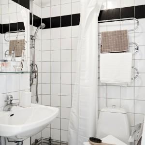 Mała, ale funkcjonalna łazienka została urządzono w dominującej w całym mieszkaniu bieli, przełamanej przez czarny pas poprowadzony pod sufitem. Fot. Stadshem.se/Janne Olander.