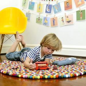 Oryginalny dywan Larry powstał z setek kolorowych pomponików, dzięki czemu jest bardzo miękki i znakomicie pełni funkcję izolatora. Fot. Happy as Larry Design.