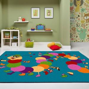Kolorowa gąsienica spacerująca po turkusowym dywanie z kolekcji Funky marki Agnella z pewnością porwie do zabawy niejednego malucha. Fot. Agnella.